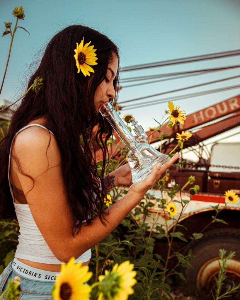 Dziewczyna pali bongo z marihuaną obok słonecznika