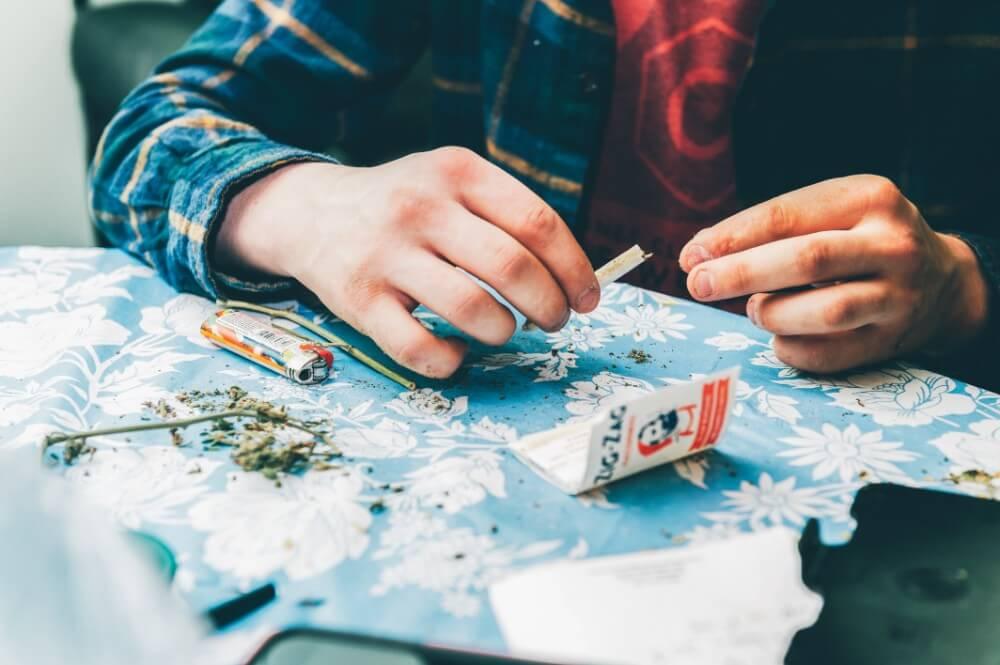 Skręcanie jointa z suszu konopnego CBD na stole z bletek i suszu